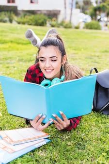 Portret van een gelukkige tiener die op het gazon ligt dat het boek leest