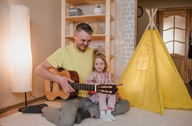 Portret van een gelukkige vader met een gitaar in zijn handen en een klein meisje, zittend op de schoot van haar vader. gezamenlijke familiespellen.