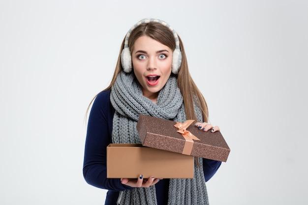 Portret van een gelukkige verbaasde vrouw met geschenkdoos geïsoleerd op een witte achtergrond