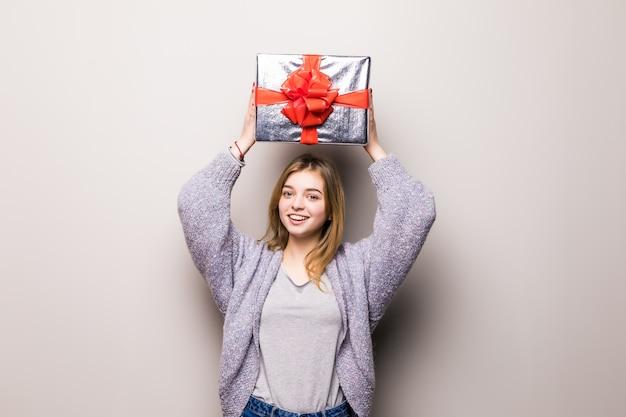 Portret van een gelukkige verbaasde vrouw met giftdoos op hoofd