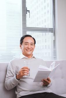 Portret van een gelukkige volwassen man die thuis een ontspannen boek leest.