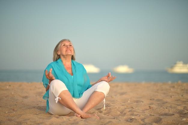 Portret van een gelukkige volwassen vrouw die mediteert op het strand