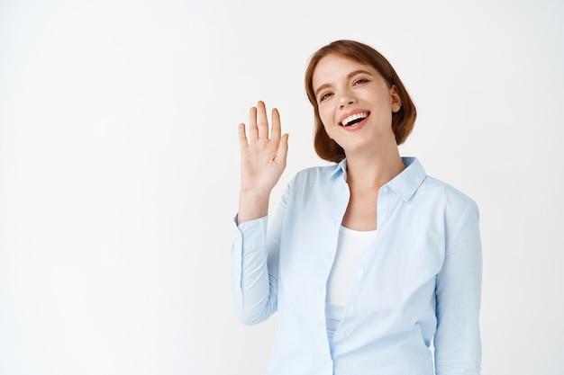 Portret van een gelukkige, vriendelijke vrouw die hallo zegt, zwaaiend met de hand hallo groetgebaar, glimlacht, staande in een kantoorblouse op een witte muur