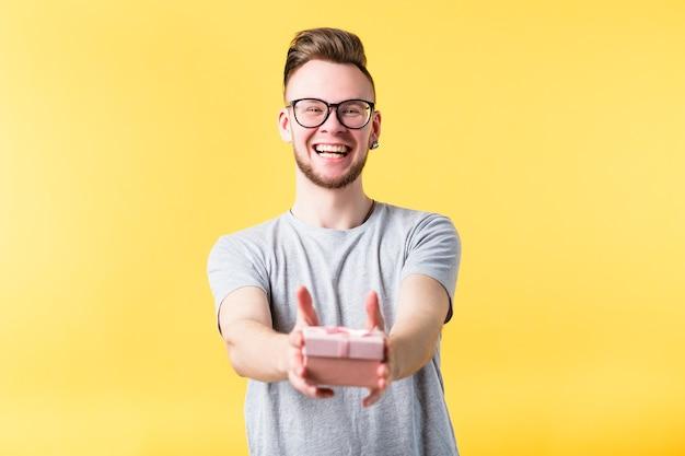 Portret van een gelukkige, vrolijke emotionele jonge kerel die lacht en een verjaardagscadeau geeft in een doos.