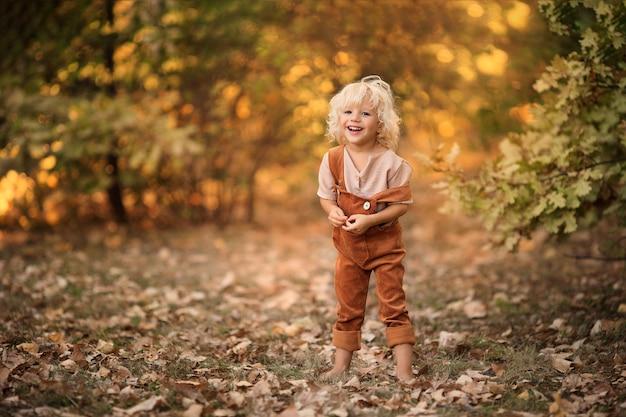 Portret van een gelukkige vrolijke jongen die in het bos loopt