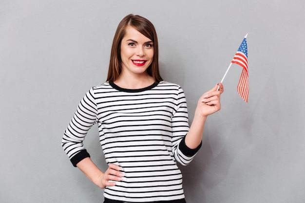 Portret van een gelukkige vrouw die amerikaanse vlag houdt