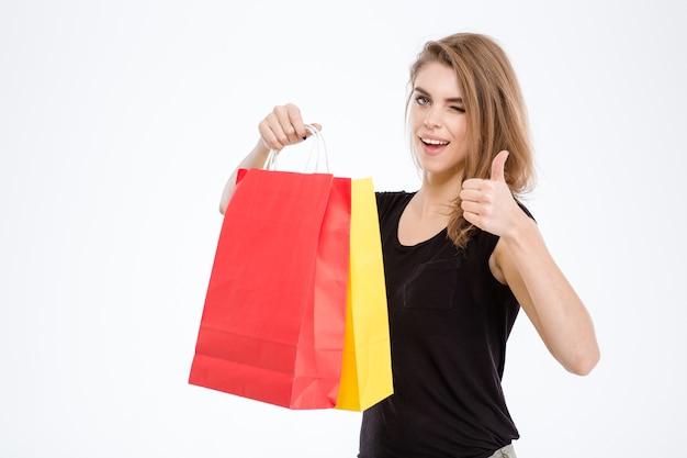 Portret van een gelukkige vrouw die boodschappentassen vasthoudt en duim toont geïsoleerd op een witte achtergrond