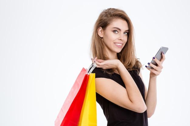Portret van een gelukkige vrouw die boodschappentassen vasthoudt en smartphone gebruikt die op een witte achtergrond wordt geïsoleerd