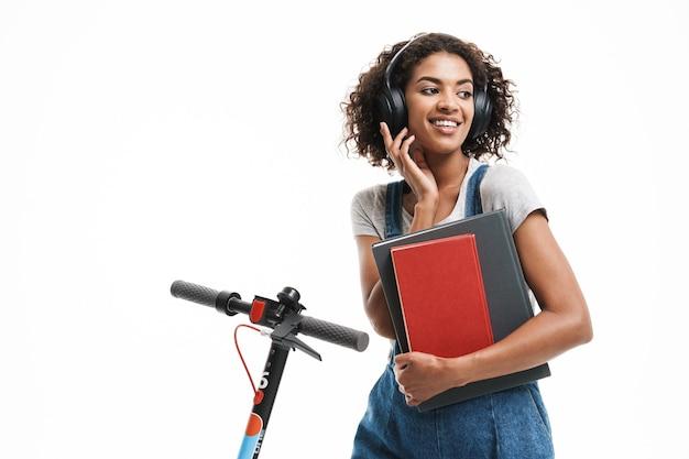 Portret van een gelukkige vrouw die een koptelefoon gebruikt en oefenboeken vasthoudt terwijl ze op een scooter rijdt, geïsoleerd over een witte muur
