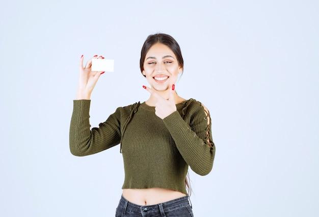 Portret van een gelukkige vrouw die een leeg visitekaartje toont.