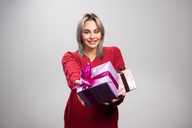 Portret van een gelukkige vrouw die geschenkdozen op een grijze achtergrond aanbiedt.