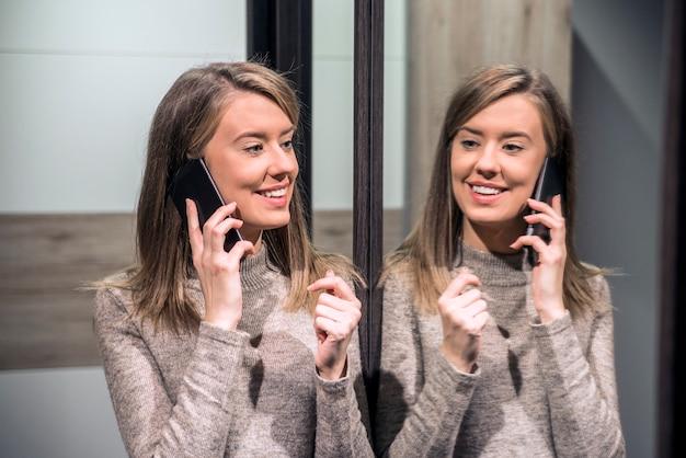 Portret van een gelukkige vrouw die haar reflectie in de spiegel bekijkt en telefonisch praten. sexy jonge vrouw bellen per telefoon
