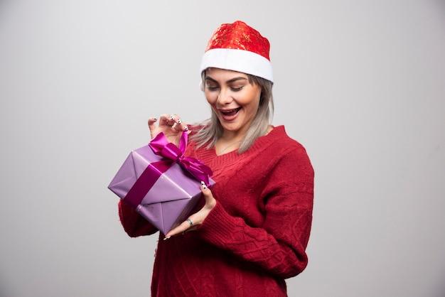 Portret van een gelukkige vrouw die haar vakantiecadeau probeert te openen.