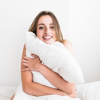 Portret van een gelukkige vrouw die hoofdkussen koestert