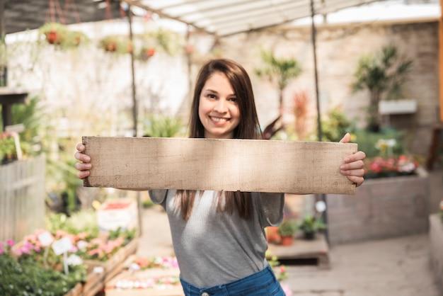 Portret van een gelukkige vrouw die houten plank houdt
