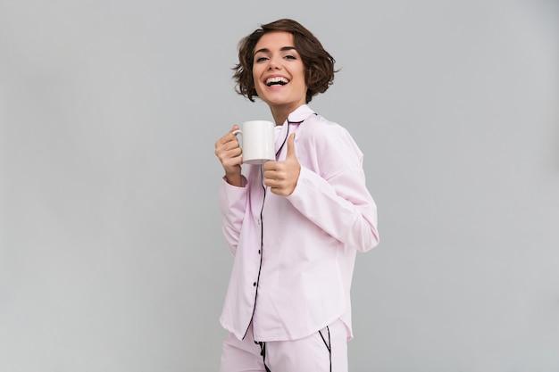 Portret van een gelukkige vrouw die in pyjama een kop houdt