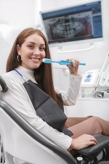 Portret van een gelukkige vrouw die in tandartsstoel grote tandenborstel houdt, toont hoe tanden te poetsen