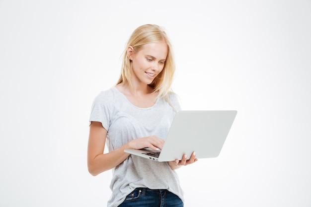 Portret van een gelukkige vrouw die laptop computer met behulp van die op een witte achtergrond wordt geïsoleerd