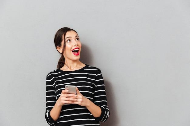 Portret van een gelukkige vrouw die mobiele telefoon houdt