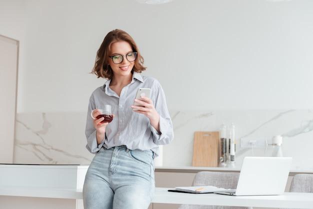 Portret van een gelukkige vrouw die mobiele telefoon met behulp van