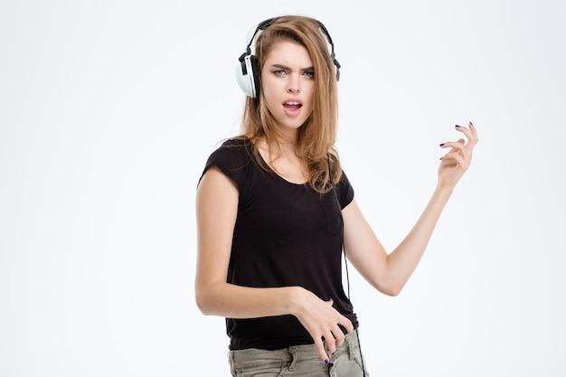 Portret van een gelukkige vrouw die muziek luistert en plezier heeft geïsoleerd op een witte achtergrond
