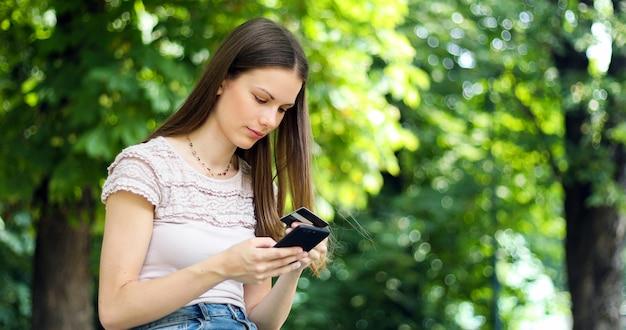 Portret van een gelukkige vrouw die online met creditcard en slimme telefoon in een park betaalt