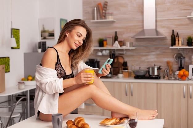 Portret van een gelukkige vrouw die op de keukentafel zit en sexy lingerie draagt. provocerende jonge vrouw met tatoeages die verleidelijk ondergoed dragen.