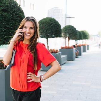 Portret van een gelukkige vrouw die op mobiele telefoon in stad spreekt