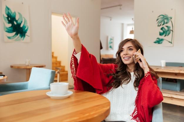 Portret van een gelukkige vrouw die op mobiele telefoon spreekt