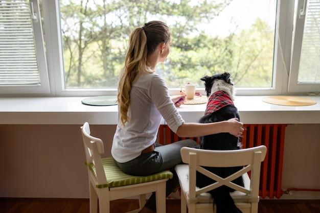 Portret van een gelukkige vrouw die thuis met haar hond speelt