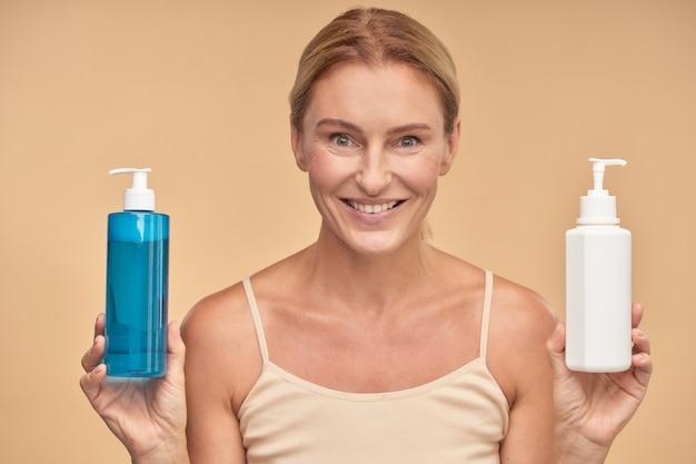 Portret van een gelukkige vrouw die tussen twee lichaamsverzorgingsproducten kiest terwijl ze geïsoleerd staat