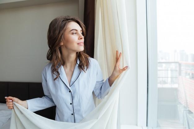 Portret van een gelukkige vrouw het openen gordijnen