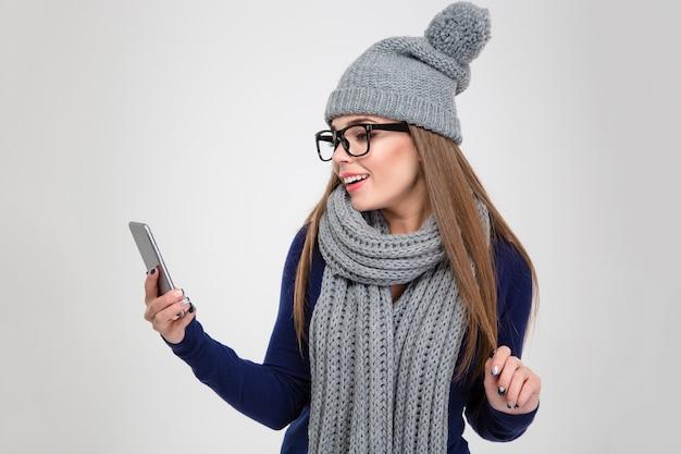 Portret van een gelukkige vrouw in de winterdoek die smartphone gebruikt die op een witte muur wordt geïsoleerd