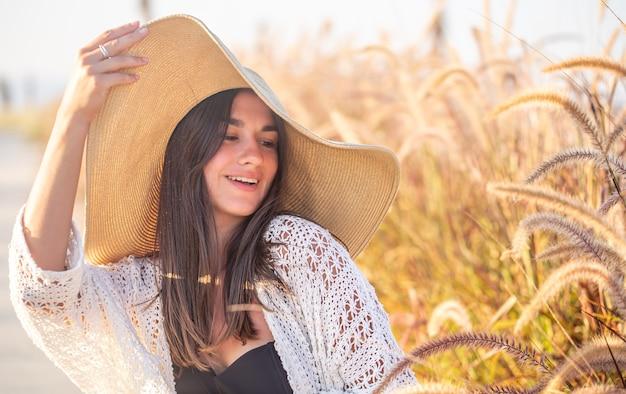 Portret van een gelukkige vrouw in de zon, zittend in een veld, gekleed in zomerkleren en een hoed.