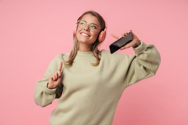 Portret van een gelukkige vrouw in een bril met een koptelefoon en een mobiele telefoon terwijl ze met de vinger naar boven wijst, geïsoleerd over roze muur