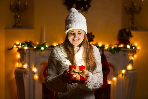 Portret van een gelukkige vrouw in een trui met een gloeiende geschenkdoos op kerstavond