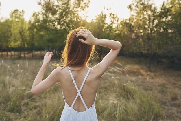Portret van een gelukkige vrouw in een zomerjurk in een veld jaar van achter de bomen zonsondergang