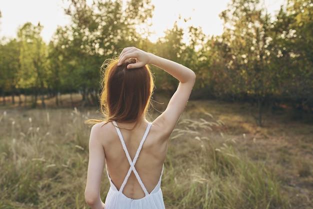 Portret van een gelukkige vrouw in een zomerjurk in een veldjaar van achter de bomen zonsondergang