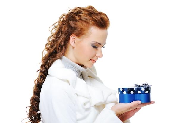 Portret van een gelukkige vrouw in witte bontjas met blauwe huidige doos