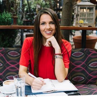 Portret van een gelukkige vrouw met agenda op bureau