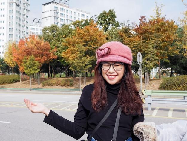 Portret van een gelukkige vrouw met een gebreide muts die in de buurt van een stadsstraat staat in de herfst