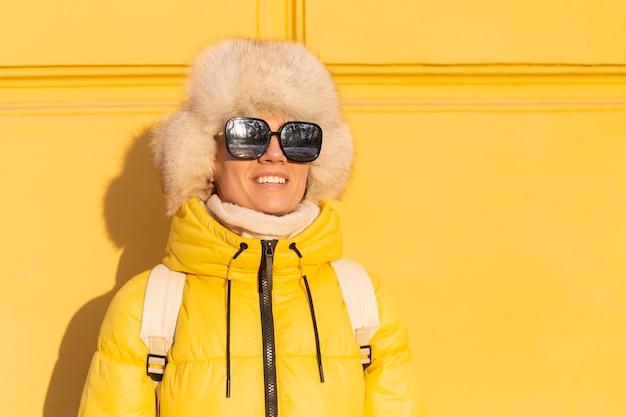 Portret van een gelukkige vrouw met een glimlach in sneeuwwitte zabas in de winter tegen een gele muur op een zonnige dag in een warme russische siberische hoed