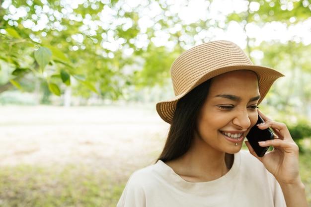 Portret van een gelukkige vrouw met een strohoed en lippiercing die praat op een smartphone in een groen park