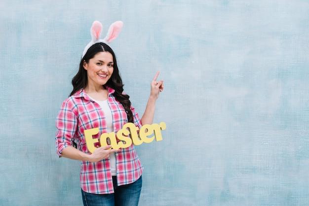 Portret van een gelukkige vrouw met konijntjesoren op hoofd die pasen-woord houden die vinger omhoog op blauwe achtergrond richten
