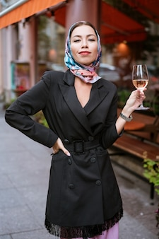 Portret van een gelukkige vrouw met make-up staat in de buurt van een café op straat met een glas wijn in haar hand