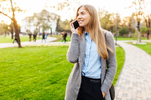 Portret van een gelukkige vrouw, staande in het park, praten aan de telefoon