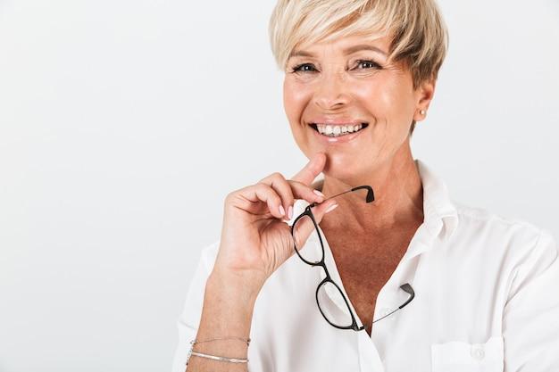 Portret van een gelukkige vrouw van middelbare leeftijd die een bril vasthoudt en naar een camera kijkt die over een witte muur in de studio wordt geïsoleerd