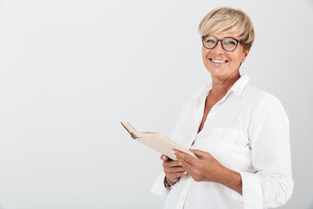 Portret van een gelukkige vrouw van middelbare leeftijd met een bril die een boek vasthoudt en naar een camera kijkt die over een witte muur in de studio is geïsoleerd;