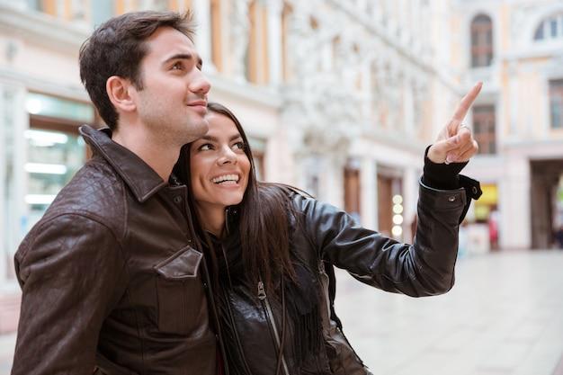 Portret van een gelukkige vrouw wijzende vinger op iets met haar vriendje buiten in europese stad