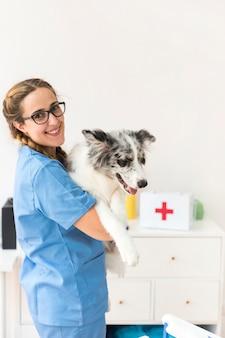 Portret van een gelukkige vrouwelijke dierenarts met hond